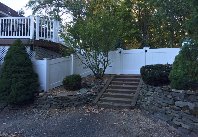 White PVC Fence Installed in Rock Wall